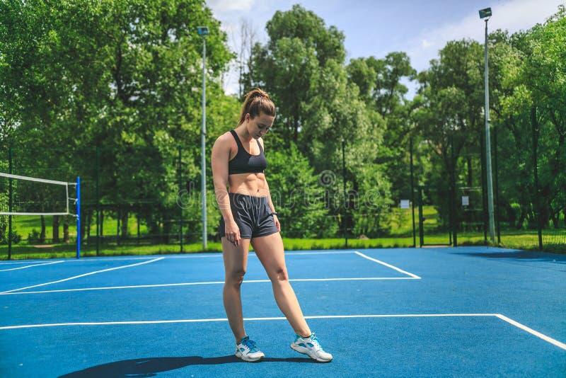 Sportieve vrouw die op haar abs op de blauwe tennisbaan in het park van Moskou kijkt Yauza stock foto