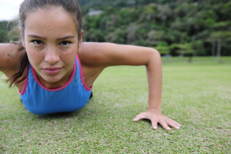 Sportieve vrouw die opdrukoefeningen doet stock afbeelding