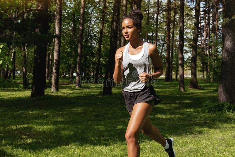 Sportieve vrouw die in park lopen stock fotografie