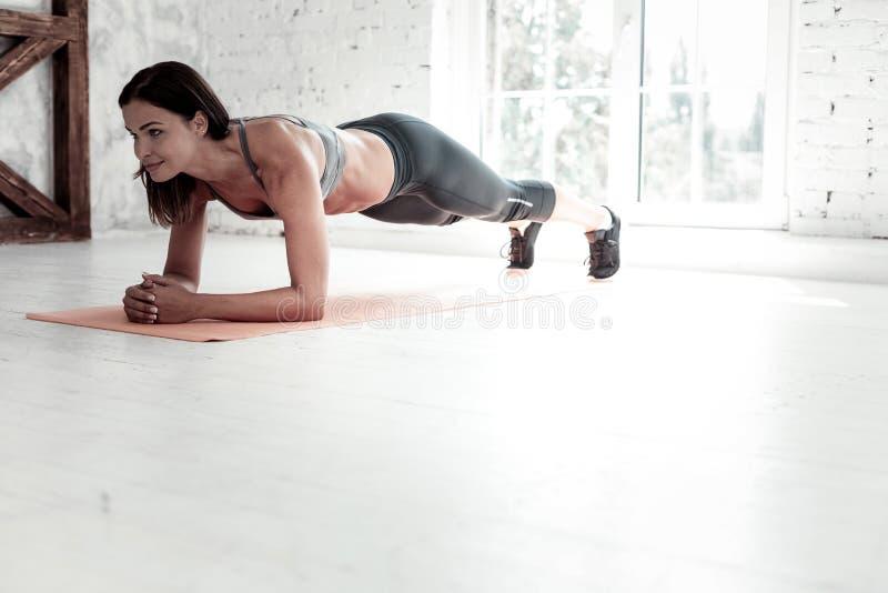 Sportieve vrouw die plankoefening doen terwijl opleiding bij gymnastiek royalty-vrije stock afbeeldingen