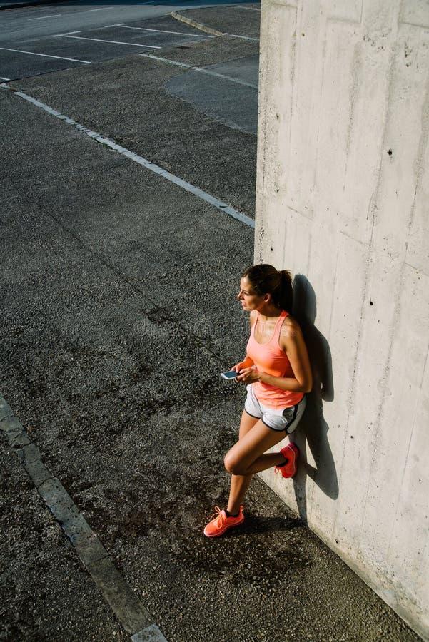 Sportieve vrouw die smartphone voor het texting gebruiken tijdens stedelijke training r royalty-vrije stock afbeeldingen