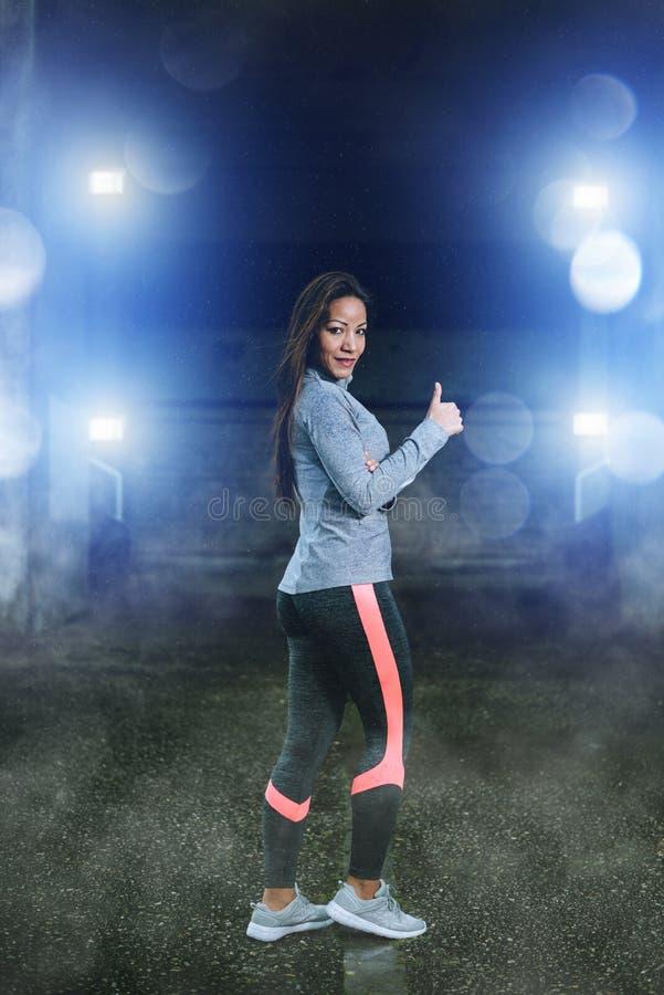 Sportieve vrouw die succesgebaar doen onder de regen na training royalty-vrije stock foto
