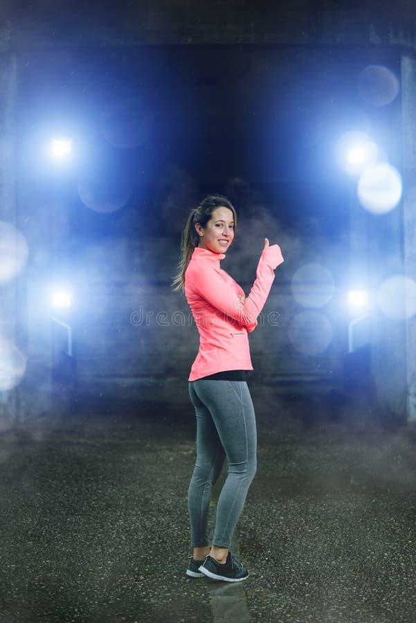 Sportieve vrouw die succesgebaar doen onder de regen na training stock foto's