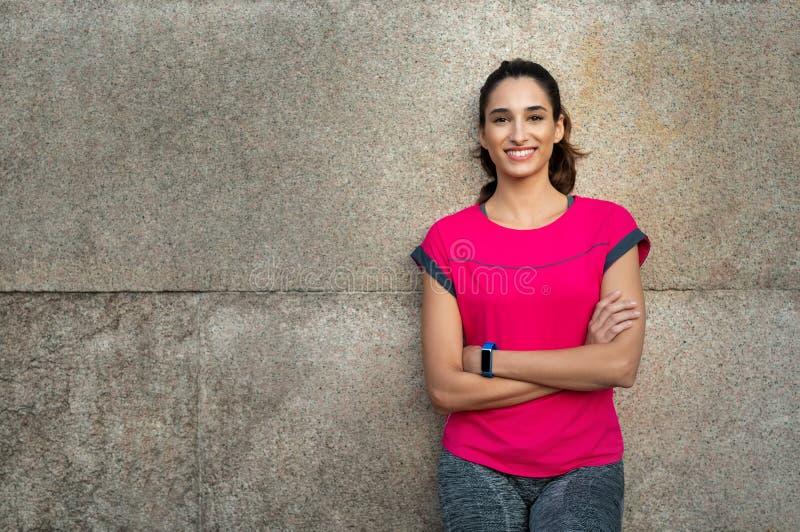 Sportieve vrouw die tegen muur leunen stock fotografie