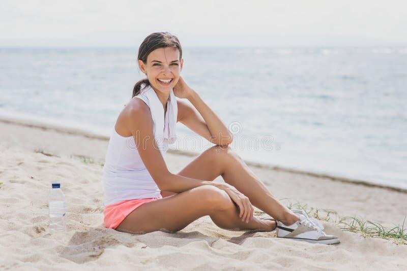 Sportieve vrouw die terwijl het zitten op het zand na training glimlachen royalty-vrije stock foto