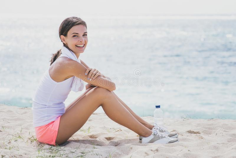 Sportieve vrouw die terwijl het zitten op het zand na training glimlachen royalty-vrije stock afbeeldingen
