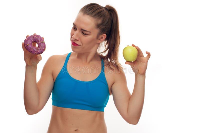 Sportieve vrouw die tussen doughnut en appel kiezen royalty-vrije stock fotografie