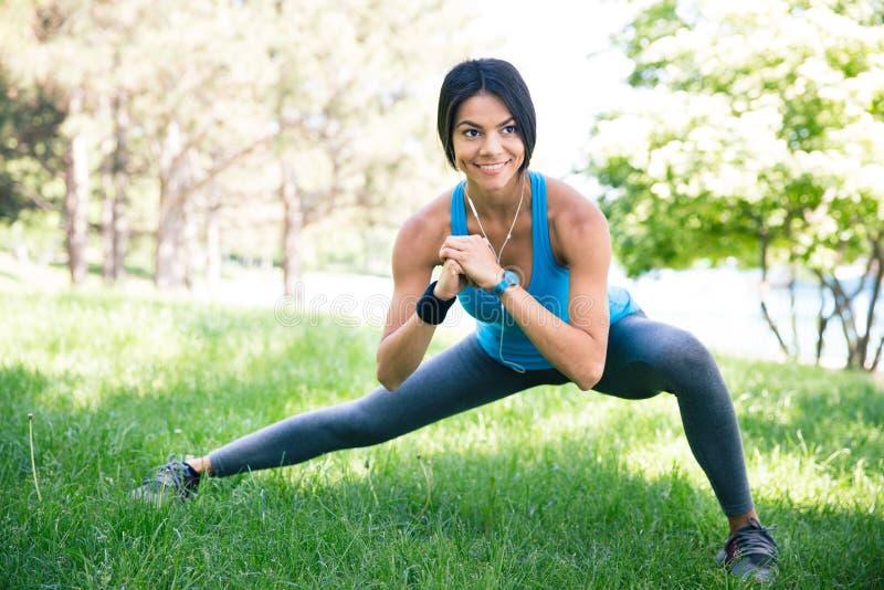 Sportieve vrouw die uitrekkende oefening doen stock fotografie