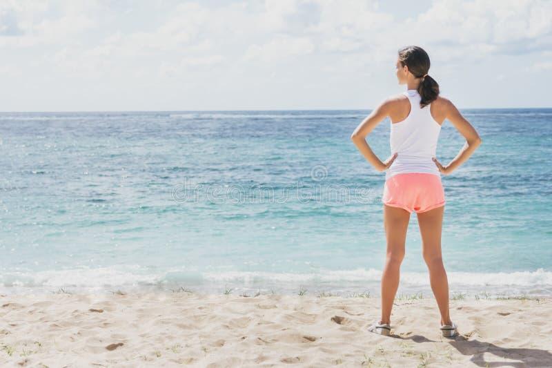 Sportieve vrouw die vóór training bij het strand opwarmen stock fotografie