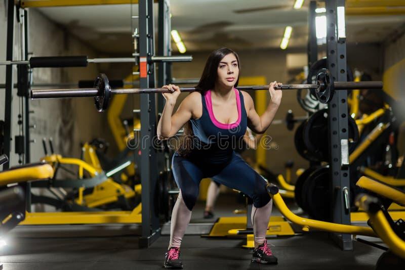 Sportieve vrouw het opheffen gewichten Geschikt meisje die de bouwspieren uitoefenen Geschiktheid en het bodybuilding royalty-vrije stock afbeelding