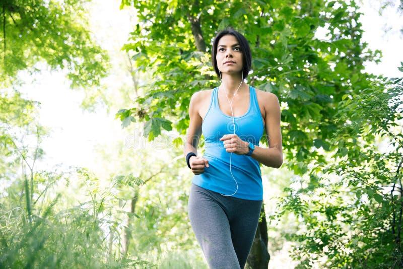 Sportieve vrouw in hoofdtelefoons die in openlucht lopen stock afbeelding