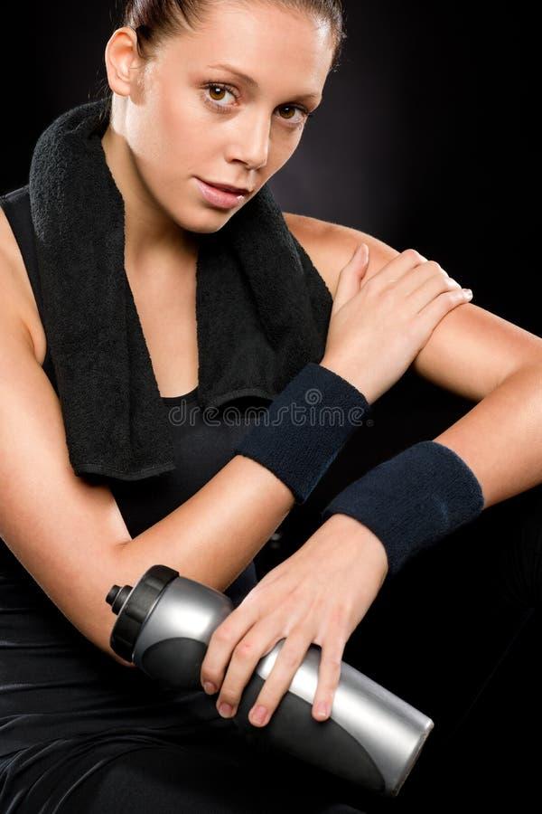 Sportieve vrouw met handdoek achter haar hals stock afbeelding