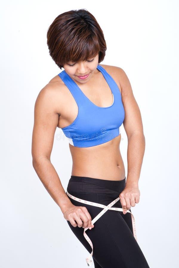 sportieve vrouw met het meten van band rond heup. stock afbeelding