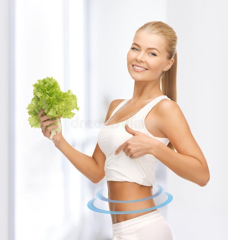 Sportieve vrouw met sla die abs tonen stock afbeelding