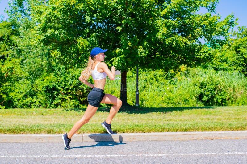 Sportieve vrouw in sportkledingssleep die op de weg lopen Het atletenmeisje stoot in het park aan stock foto