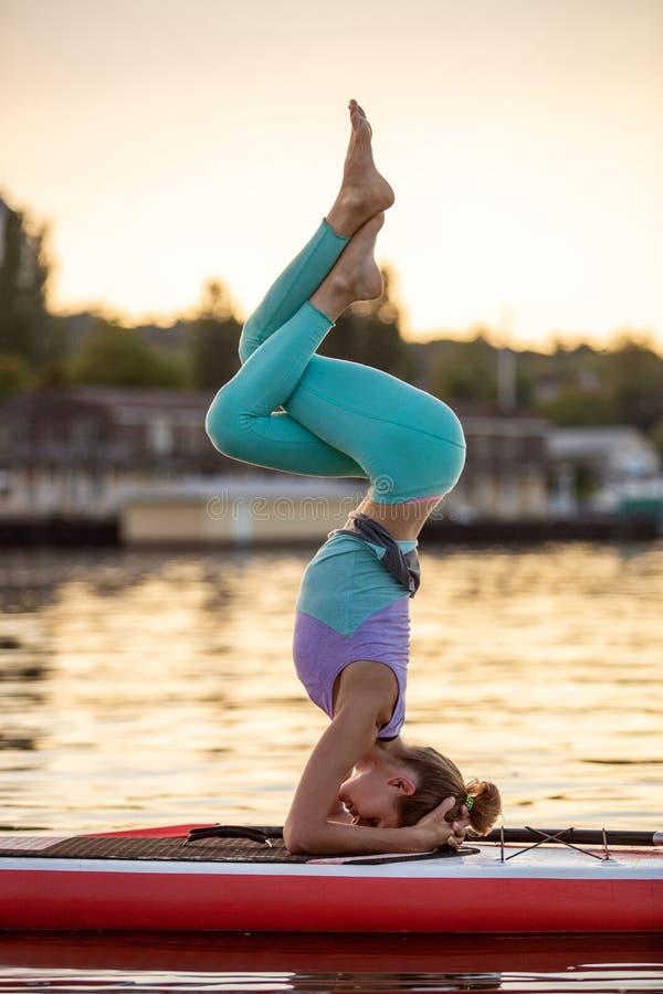 Sportieve vrouw in yogapositie inzake paddleboard, die yoga op sup raad, oefening voor flexibiliteit en het uitrekken doen zich v royalty-vrije stock foto's