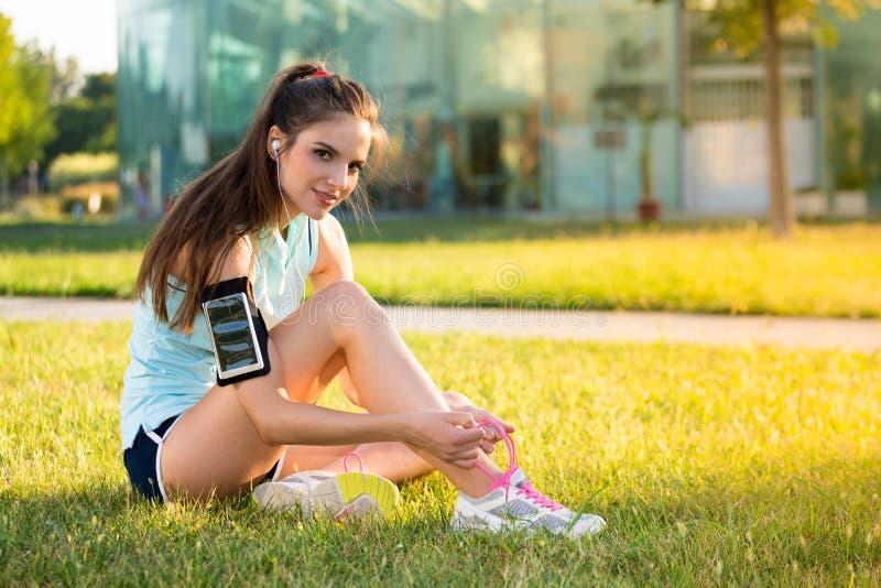 Sportieve vrouwen bindende schoenveters terwijl het luisteren aan muziek stock afbeelding