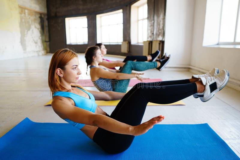 Sportieve vrouwen die oefening in gymnastiek samen doen royalty-vrije stock fotografie