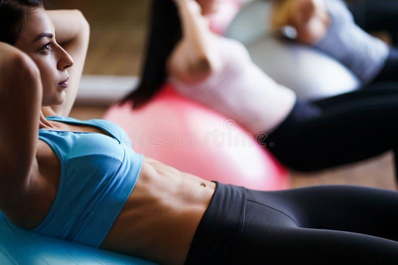 Sportieve vrouwen die pilates oefening op geschikt-ballen doen stock foto