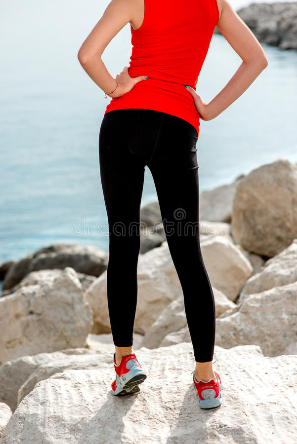 Sportieve vrouwenbenen op het rotsachtige strand stock afbeelding