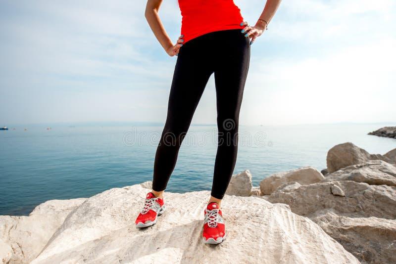 Sportieve vrouwenbenen op het rotsachtige strand royalty-vrije stock afbeeldingen