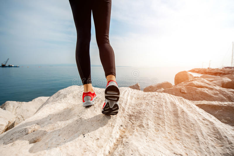 Sportieve vrouwenbenen op het rotsachtige strand stock foto