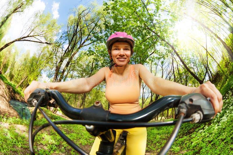 Sportieve vrouwenholding op stuur van haar fiets stock foto's
