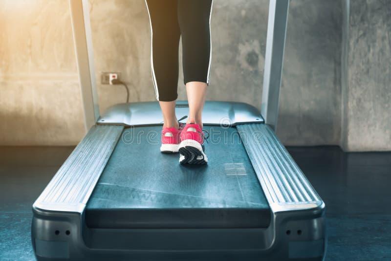 Sportieve vrouwenoefening die op tredmolenmachine lopen in geschiktheidsgymnastiek , Close-up van agentschoenen op spoor, Geschik royalty-vrije stock foto