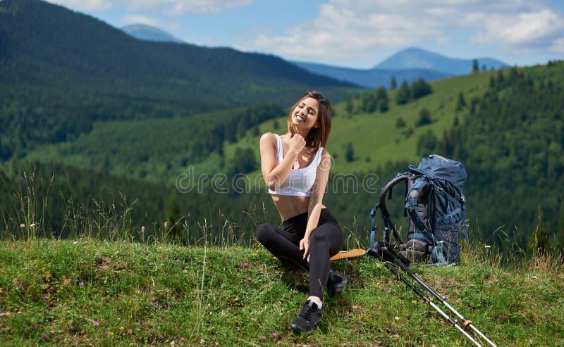 Sportieve vrouwenwandelaar met rugzak die in de bergen rusten stock foto's