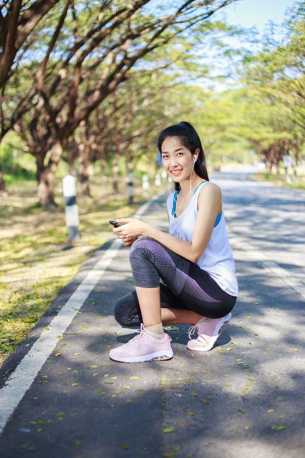Sportieve vrouwenzitting op de weg in het park en het gebruiken smartphon stock foto