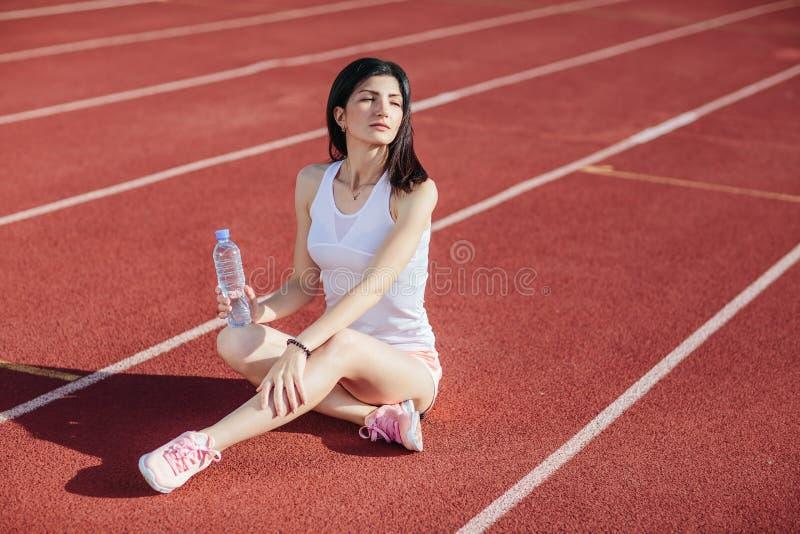 Sportieve vrouwenzitting op tredmolen met fles water royalty-vrije stock afbeelding