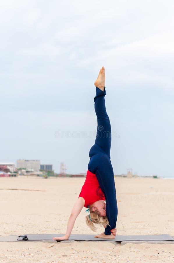 Sportieve womang Gesteunde Headstand, yogaasana op kustachtergrond royalty-vrije stock foto's