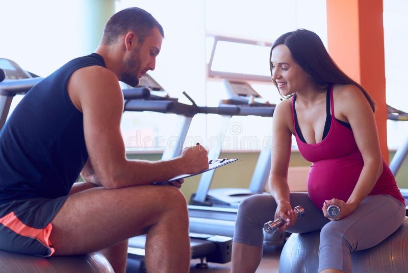 Sportieve zwangere vrouw die van resultaten met persoonlijke trainer nota nemen stock fotografie