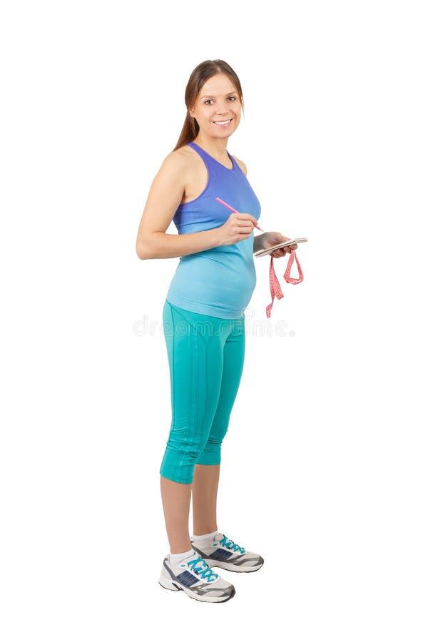 Sportieve zwangere vrouw met een notitieboekje en een meetlint royalty-vrije stock foto's