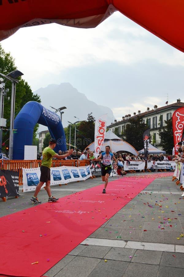"""Sportif arrivant à la finition """"ville de Lecco - d'événement courant de marathon de montagne de Resegone """" photographie stock"""