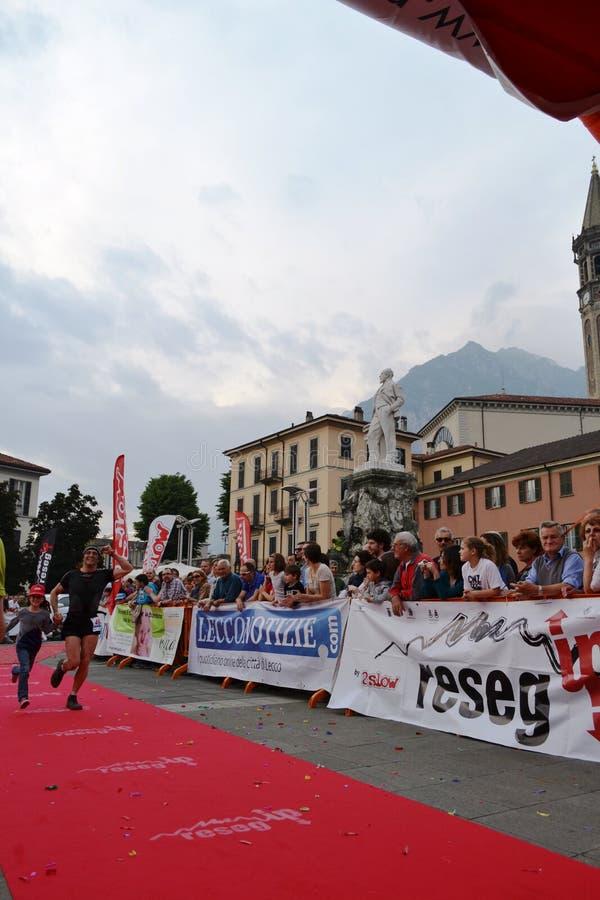 """Sportif arrivant à la finition """"ville de Lecco - d'événement courant de marathon de montagne de Resegone """" image stock"""