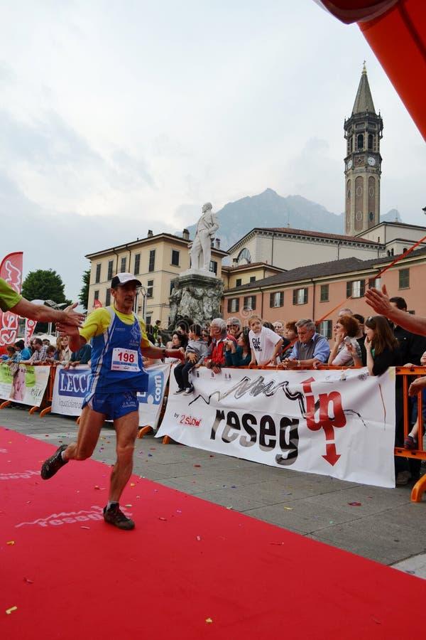 """Sportif arrivant à la finition """"ville de Lecco - d'événement courant de marathon de montagne de Resegone """" image libre de droits"""