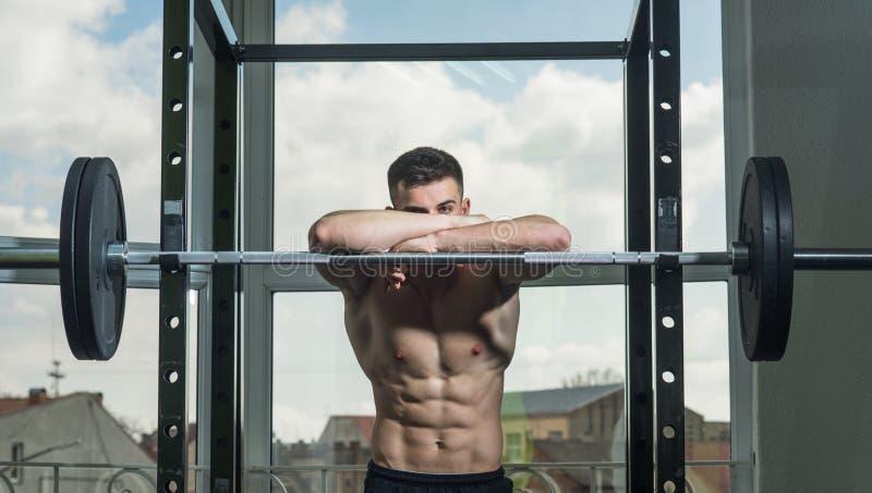 Sportif, athlète avec des sembler de muscles attrayants Homme avec le torse, maigre musculaire de macho sur le barbell, fenêtre s photos stock