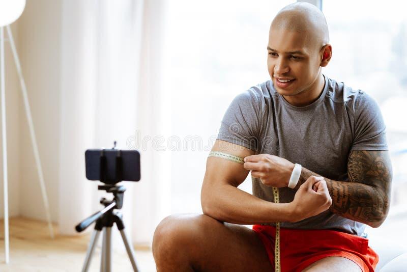 Sportif aux yeux noirs employant le ruban m?trique tout en mesurant le biceps photographie stock