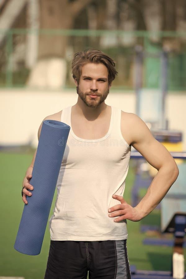 Sportif avec le tapis bleu de yoga dans des mains fortes photographie stock libre de droits