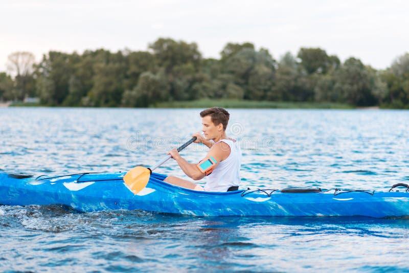 Sportif beau fort appréciant son temps tout en ramant dans le canoë images libres de droits