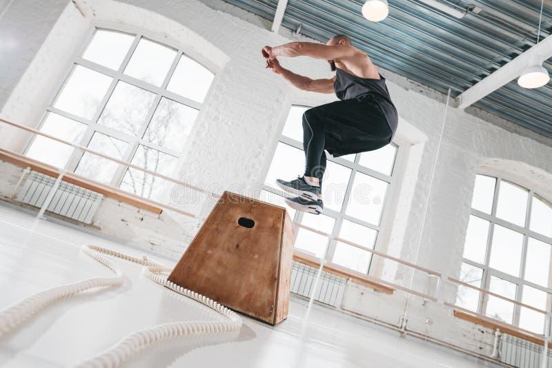 Sportif d'ajustement faisant des exercices de saut sur la boîte en bois dans le gymnase croisé de séance d'entraînement photos libres de droits