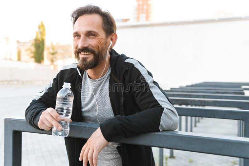 Sportif mûr fort beau tenant la bouteille avec de l'eau photographie stock