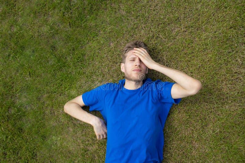 Sportif masculin fatigué d'athlète détendre sur le champ d'herbe après des pratiques photo stock