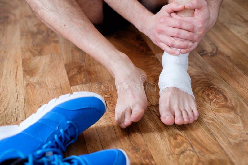 Sportif massant sa cheville blessée photos stock