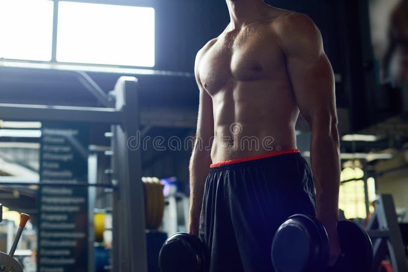 Sportif musculaire posant dans le gymnase photographie stock