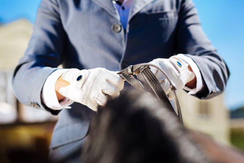 Sportif portant les gants bleus étant prêts pour l'équitation photos stock