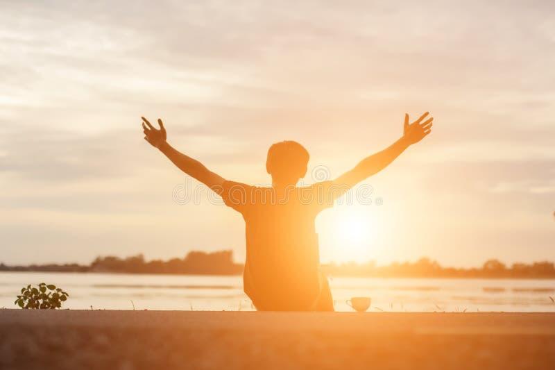 Sportif r?ussi soulevant des bras l'?t? d'or de coucher du soleil d'?clairage de dos de ciel apr?s le fonctionnement crois? Athlè photo stock