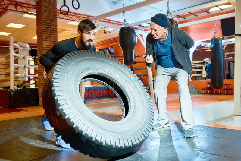 Sportif renversant le pneu avec l'entraîneur près image stock