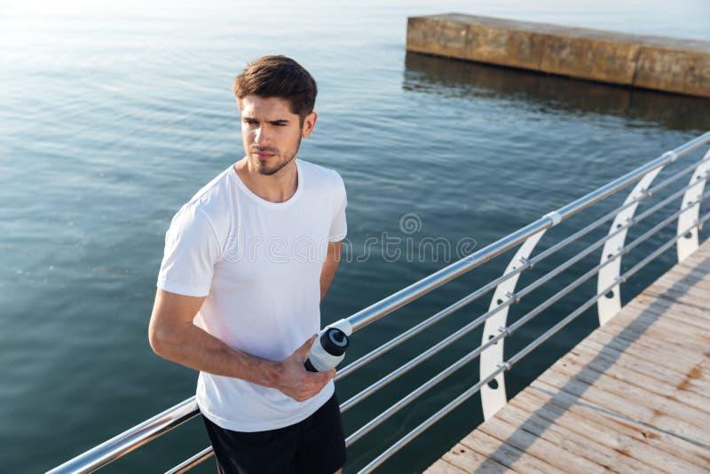 Sportif se tenant près de la mer et de l'eau potable  photos stock